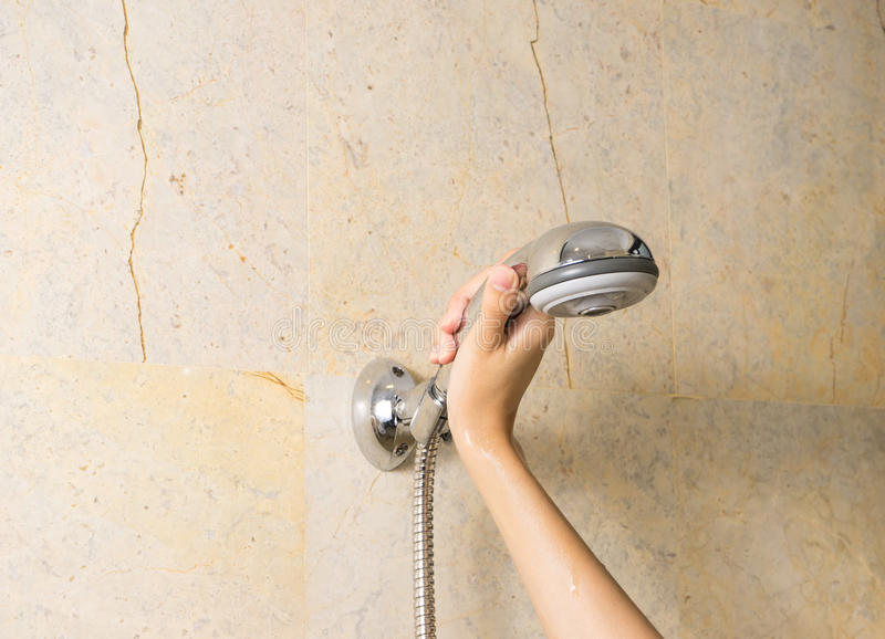La mano tiene una doccia sul fondo dei marmi fotografie stock libere da diritti