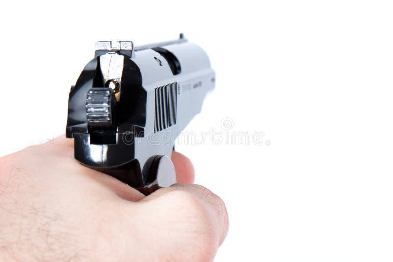 La mano tiene una pistola su un fondo bianco immagini stock libere da diritti