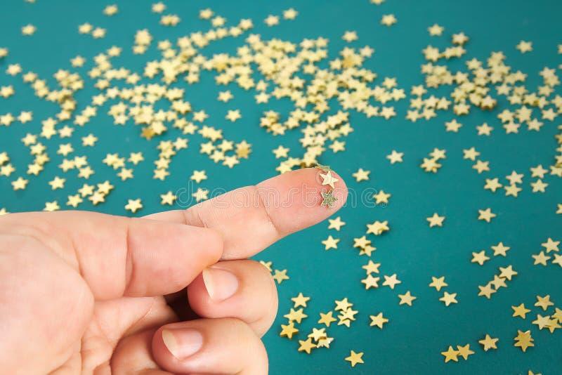 La mano toca confeti sólido en las estrellas de la forma El concepto de tacto, tactility, sensaciones fotografía de archivo libre de regalías