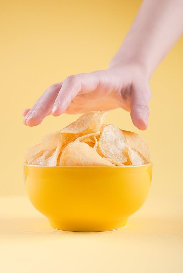 La mano toma las patatas fritas ab imagen de archivo
