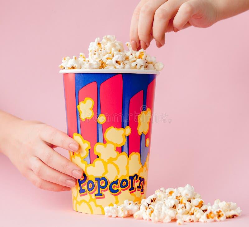 La mano toma palomitas de una taza de papel en un fondo rosado La mujer come las palomitas Concepto del cine Endecha plana Copysp fotografía de archivo libre de regalías