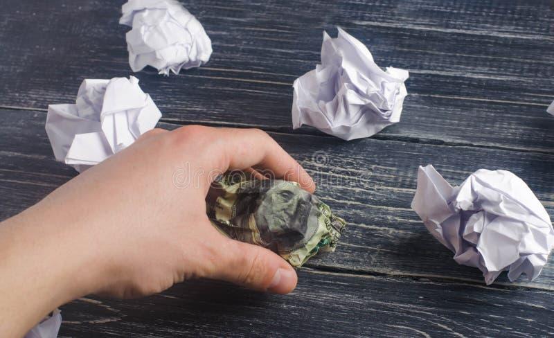 La mano toma un dólar arrugado en las manos de las bolas del Libro Blanco proceso de pensar y de encontrar nuevas ideas del negoc imagen de archivo libre de regalías