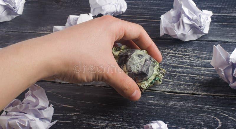 La mano toma un dólar arrugado en las manos de las bolas del Libro Blanco proceso de pensar y de encontrar nuevas ideas del negoc fotos de archivo libres de regalías