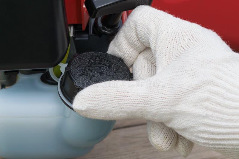 La mano torce il cappuccio del carro armato con benzina, primo piano fotografia stock libera da diritti