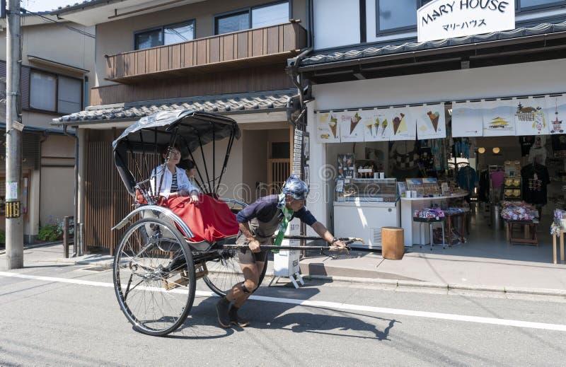 La mano tradicional japonesa tiró de turistas que llevaban del carrito en la calle de Matsubara en Kyoto, Japón imagen de archivo
