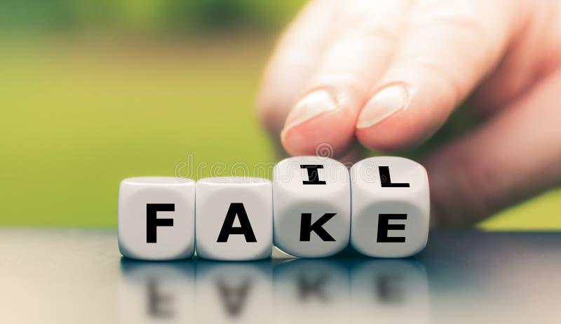 La mano trasforma un dado e cambia la parola 'falso' in 'fail immagini stock libere da diritti