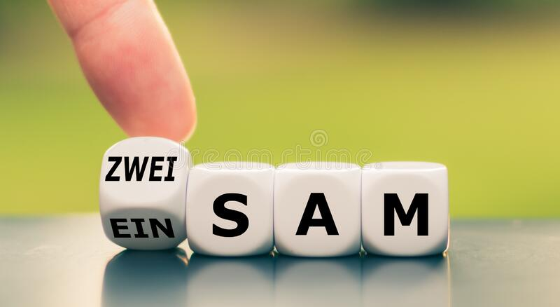 La mano trasforma un dado e cambia la parola tedesca 'einsam` `alone` in inglese in 'zweisam` `twosome` in inglese fotografia stock libera da diritti