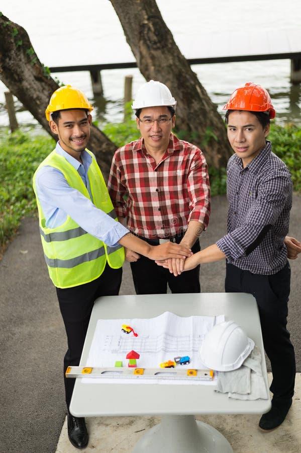 La mano tre degli ingegneri prende la coordinazione e guarda alla macchina fotografica per fa un accordo nell'investimento circa  immagine stock
