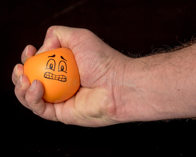 La mano umana schiaccia una palla di sforzo fotografia stock libera da diritti