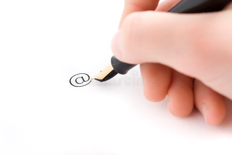 La mano y la pluma escriben la muestra del email foto de archivo