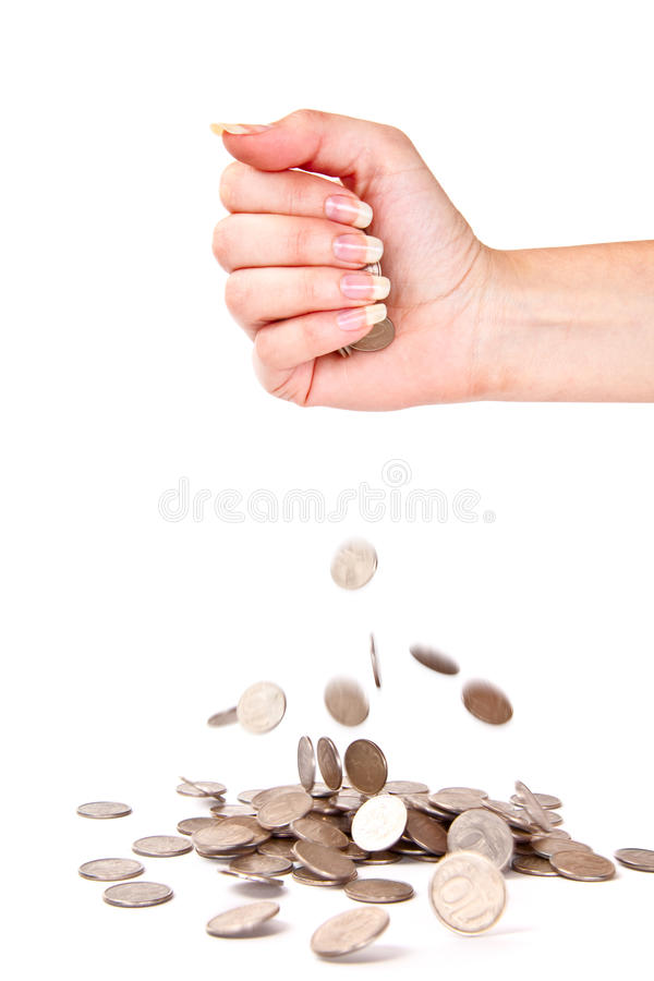 La mano y las monedas están fallando abajo imagenes de archivo