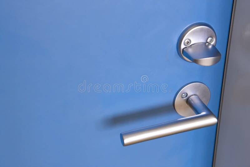 La manopola di porta metallica con fissa una porta blu immagine stock libera da diritti
