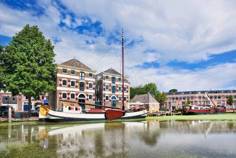 La mansión antigua con un blanco amarró el barco duplicado en un canal, Gouda, Países Bajos imágenes de archivo libres de regalías