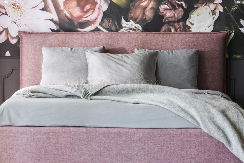 La manta y los amortiguadores grises en cama rosada en interior femenino del dormitorio con las flores wallpaper Foto verdadera imagen de archivo libre de regalías