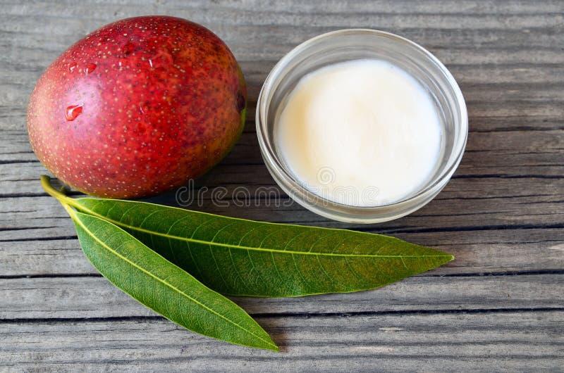 La mantequilla del cuerpo del mango en un bol de vidrio y el mango orgánico maduro fresco dan fruto y las hojas en viejo fondo de fotos de archivo