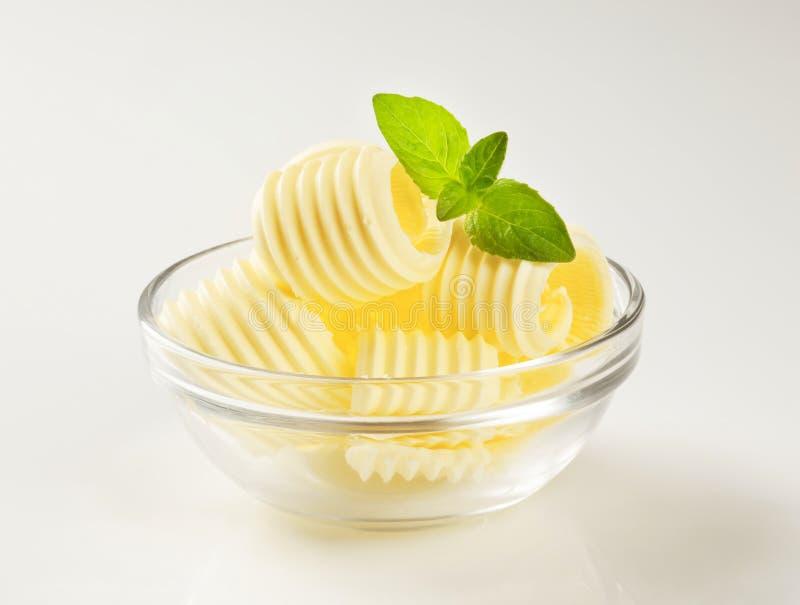 La mantequilla se encrespa en un tazón de fuente de cristal imagenes de archivo
