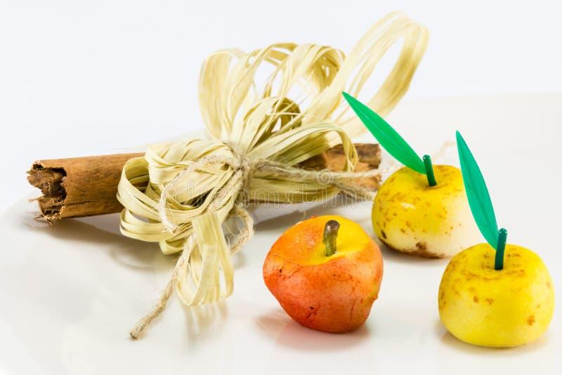 La manzana dulce del mazapán da fruto con la decoración picante del palillo del canela foto de archivo