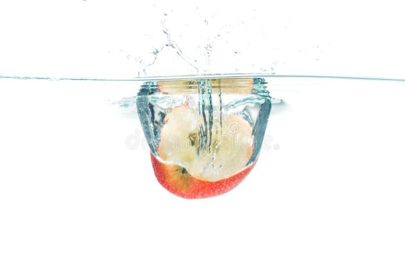 La manzana roja cayó en el agua con el chapoteo del agua en los vagos blancos fotografía de archivo libre de regalías