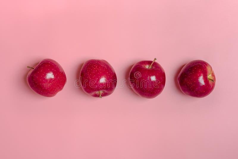 La manzana roja cosechada fresca miente en fondo milenario del rosa de la tendencia Fruta con la vitamina C, queratina Orgánico n imagenes de archivo