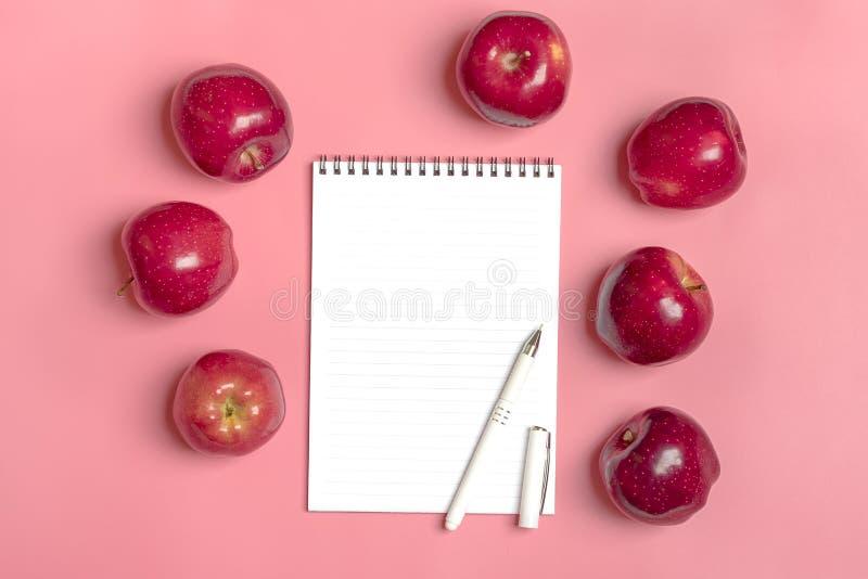 La manzana roja cosechada fresca miente en fondo milenario del rosa de la tendencia Fruta con la vitamina C, queratina Orgánico n fotografía de archivo libre de regalías