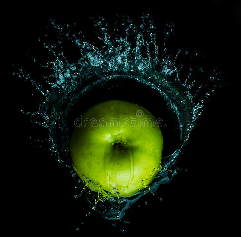 La manzana roja fresca con las gotitas del agua contra la reflexión negra del fondo cae foto de archivo
