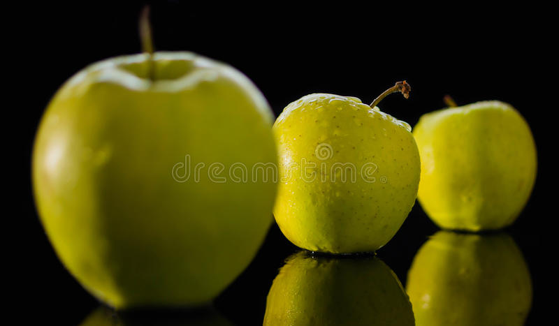 La manzana roja fresca con las gotitas del agua contra la reflexión negra del fondo cae fotos de archivo
