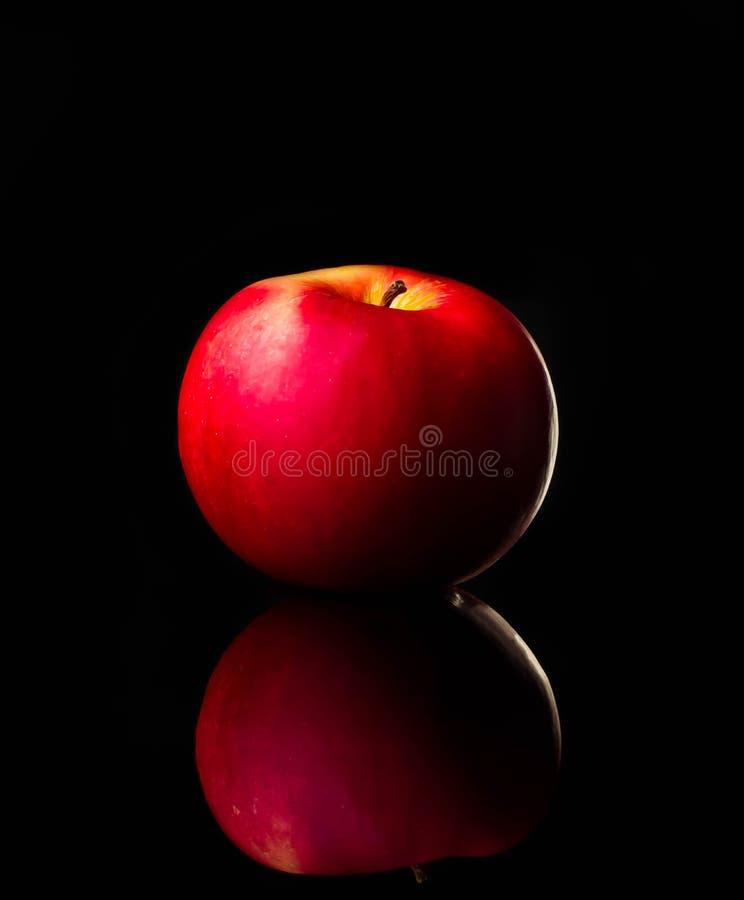 La manzana roja fresca con las gotitas del agua contra la reflexión negra del fondo cae el movimiento fresco de la acción del cha fotos de archivo