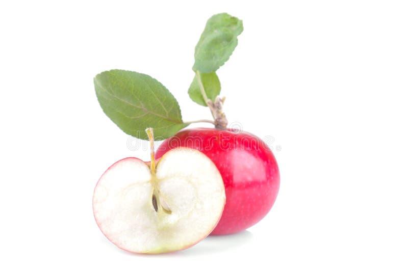 La manzana roja y la mitad de la manzana con las hojas del verde en blanco aislaron el fondo fotos de archivo
