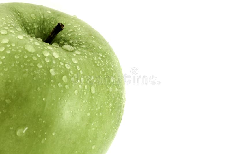 La manzana verde con el primer de las gotitas de agua tiró en blanco con el espacio de la copia para el texto fotografía de archivo
