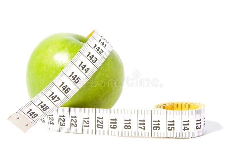 La manzana verde con medida-sujeta con cinta adhesiva foto de archivo