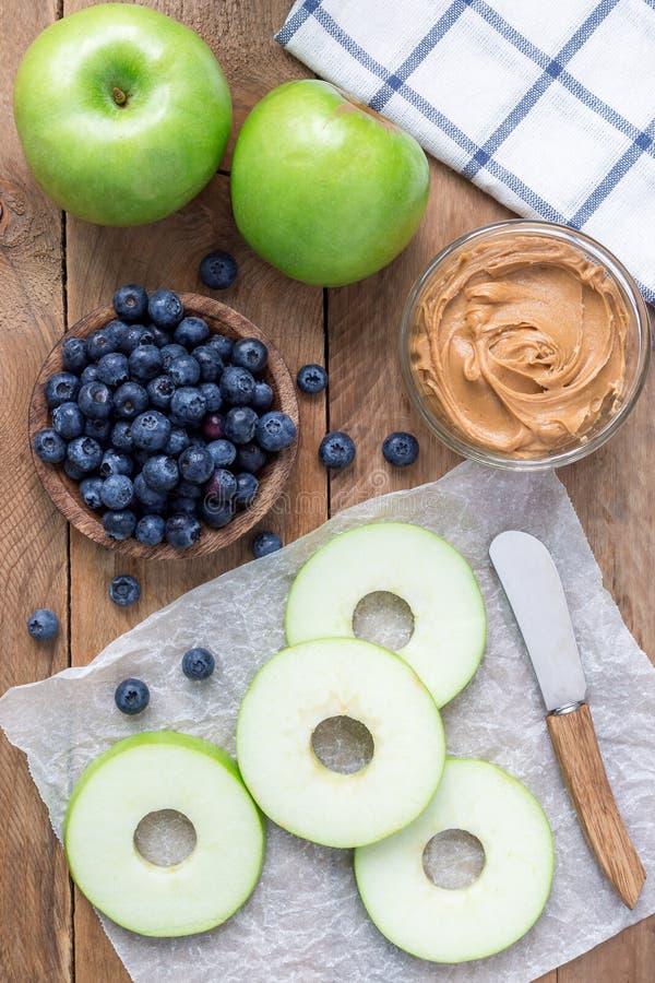 La manzana verde redondea con mantequilla de cacahuete y y arándanos en la tabla de madera, vertical, visión superior imágenes de archivo libres de regalías