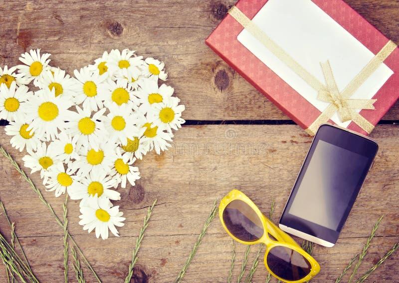 La manzanilla florece como corazón con la caja y el smartphone de regalo foto de archivo libre de regalías