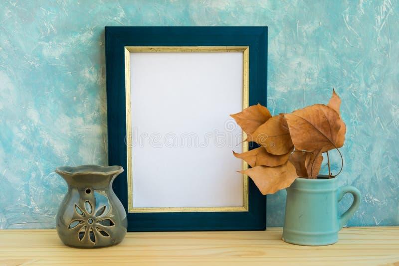 La maqueta azul y de oro del marco, fondo del muro de cemento, tabla de madera, fritada se va, lámpara de la terapia del aroma, o imagen de archivo