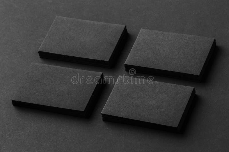 La maqueta de cuatro pilas negras de las tarjetas de visita arregló en filas en b imagen de archivo