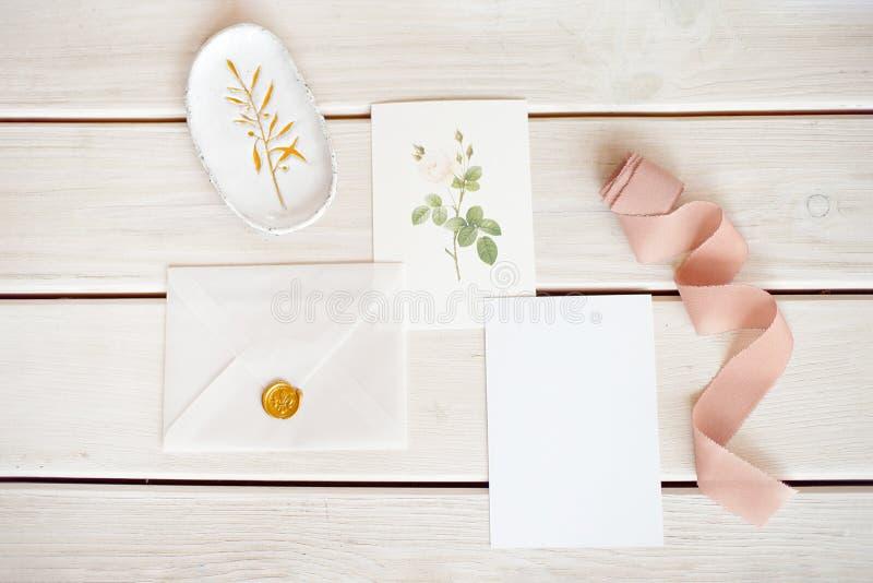 La maqueta de escritorio de la boda femenina con la tarjeta de papel en blanco y el populus del eucalipto ramifican en el fondo l foto de archivo libre de regalías