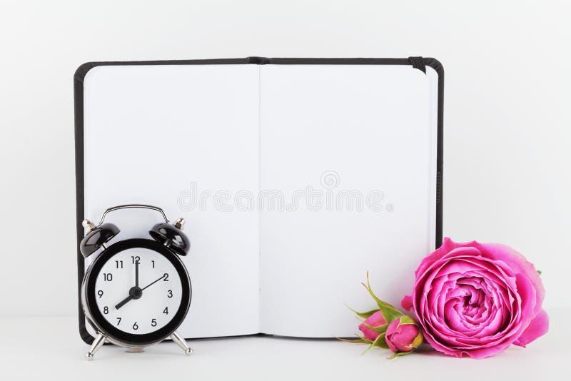 La maqueta de la flor color de rosa adornada cuaderno y el despertador en el fondo blanco con el espacio limpio para el texto y d fotografía de archivo libre de regalías