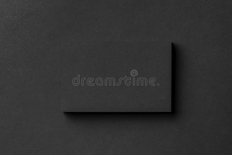 La maqueta de la pila en blanco de la tarjeta de visita en el negro texturizó el fondo imagenes de archivo