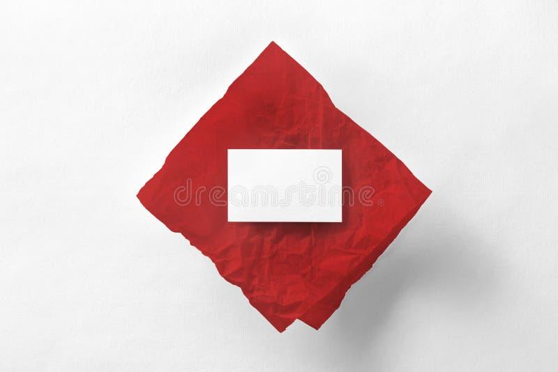 La maqueta de la tarjeta de visita en el papel de trazo rojo en el blanco texturizó p imagen de archivo