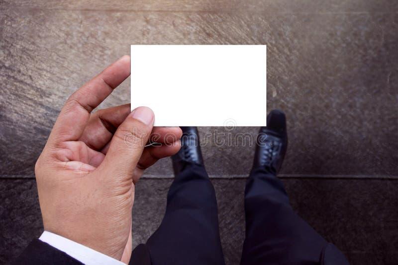 La maqueta de la tarjeta de visita en el hombre de negocios Hand, el Libro Blanco aisló w foto de archivo libre de regalías