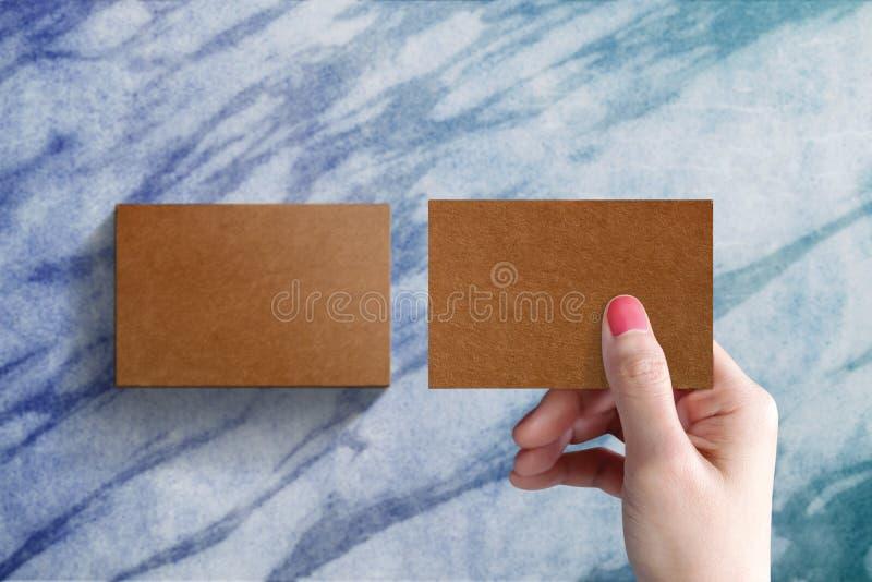 La maqueta de la tarjeta de visita presente por la mujer entrega la tabla de mármol imagenes de archivo