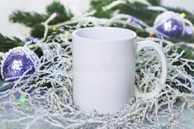 La maquette de la tasse blanche ou la tasse pour des cadeaux d'hiver conçoivent, Joyeux Noël, bonne année images libres de droits