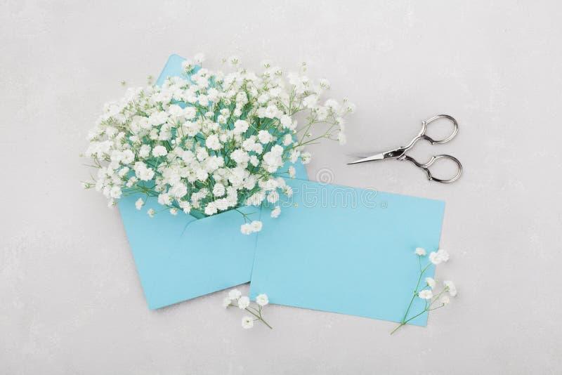 La maquette du gypsophila fleurit dans l'enveloppe et la carte de papier bleue sur la vue supérieure légère de table dans l'appar images libres de droits
