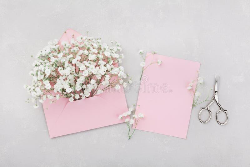 La maquette du gypsophila fleurit dans l'enveloppe et la carte de papier de rose sur la vue supérieure grise de table dans l'appa images stock