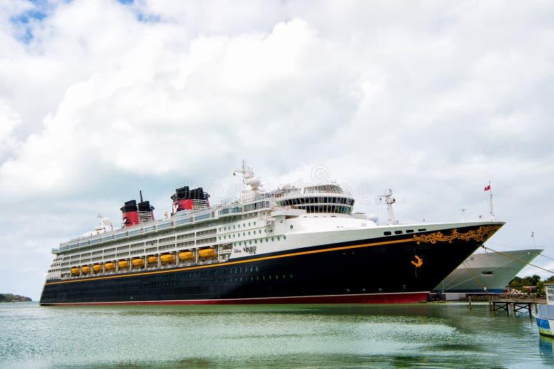 La maravilla de lujo grande de Disney del barco de cruceros en fondo de la agua de mar y del cielo nublado atracó en el puerto de imagen de archivo libre de regalías