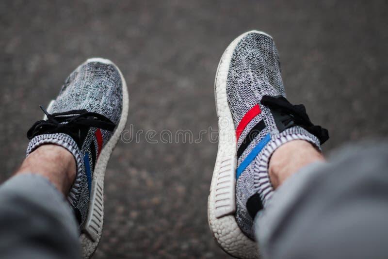 La marca adidas sta mettendo in evidenza costantemente le nuove collezioni della scarpa Uno della scarpa là alla moda è il nmd di fotografia stock