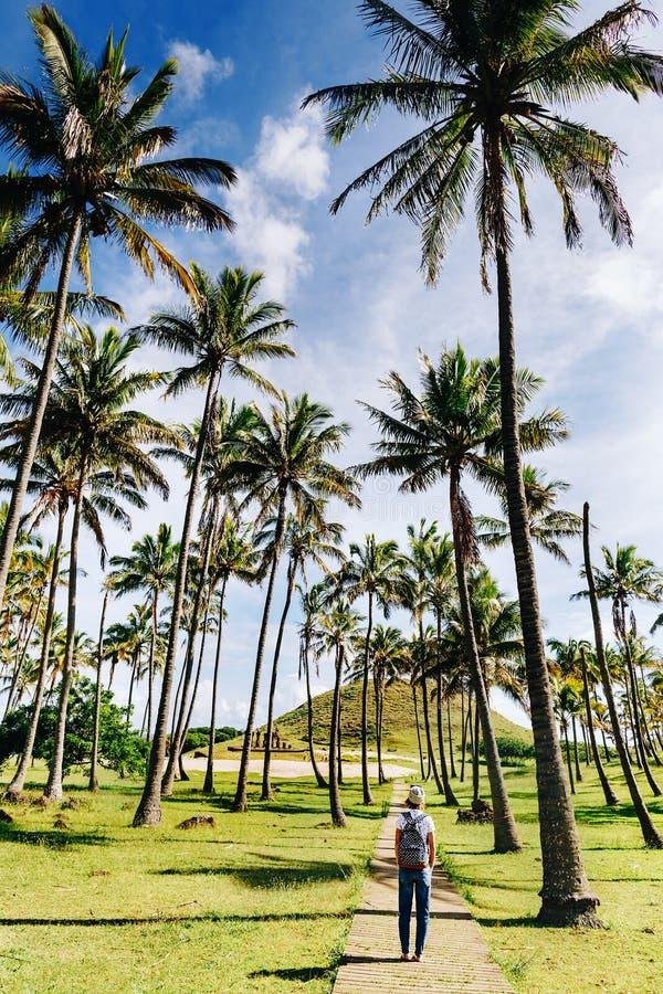 La marche heureuse de gitl de hippie bitween des palmiers sur la plage d'Anakena, île de Pâques photographie stock libre de droits