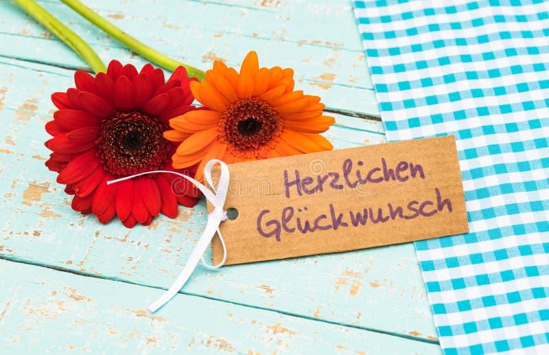 La margarita del Gerbera florece con la tarjeta de felicitación y el texto alemán, Herzlichen Glueckwunsch, enhorabuena de los me imagen de archivo libre de regalías