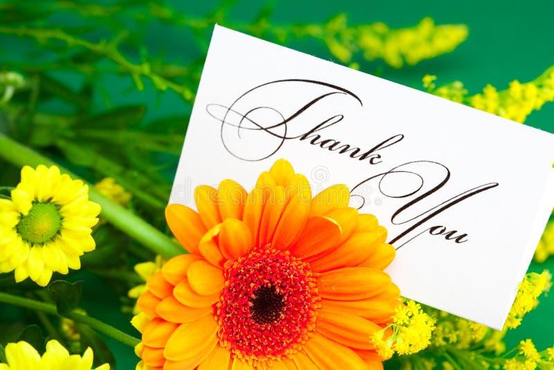 La margarita, el gerbera amarillo y la tarjeta firmados le agradecen fotografía de archivo libre de regalías