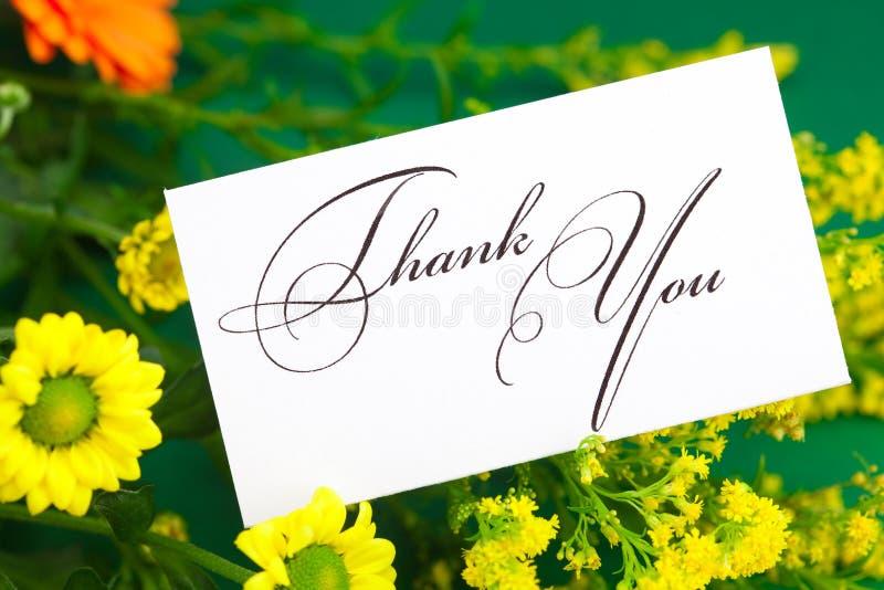 La margarita, el gerbera amarillo y la tarjeta firmados le agradecen imagen de archivo