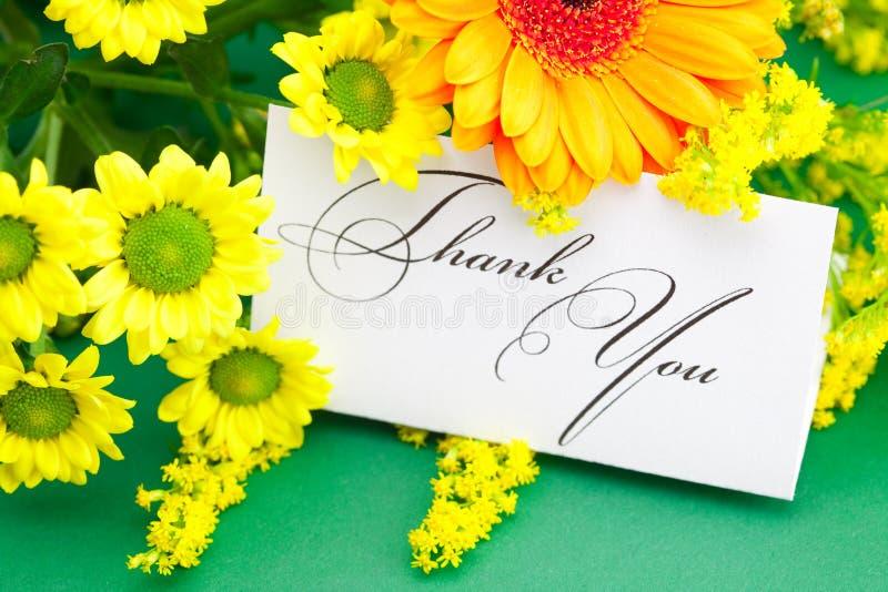 La margarita, el gerbera y la tarjeta firmados le agradecen fotos de archivo